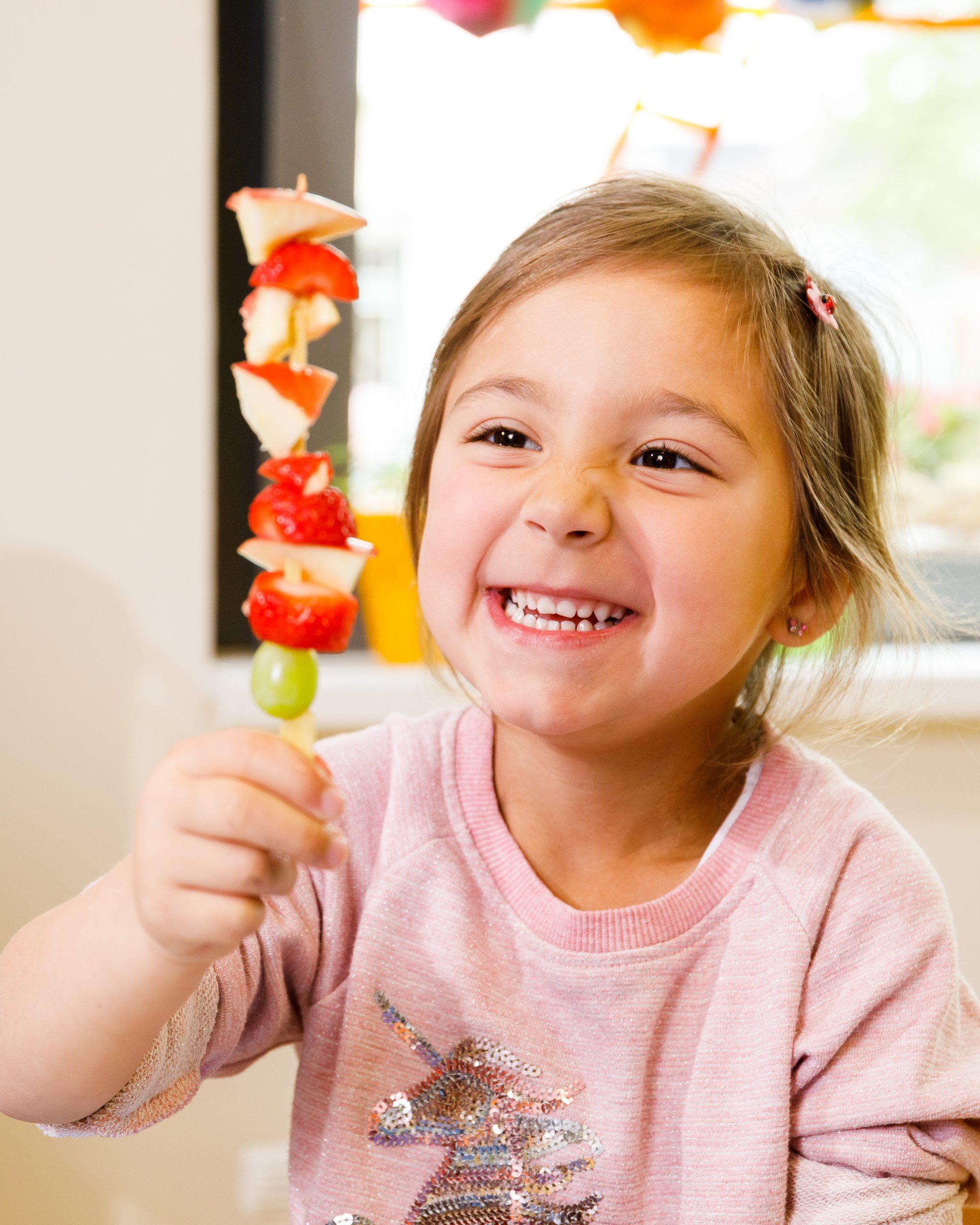 Ein Mädchen hat einen Spieß mit Obststückchen in der Hand.