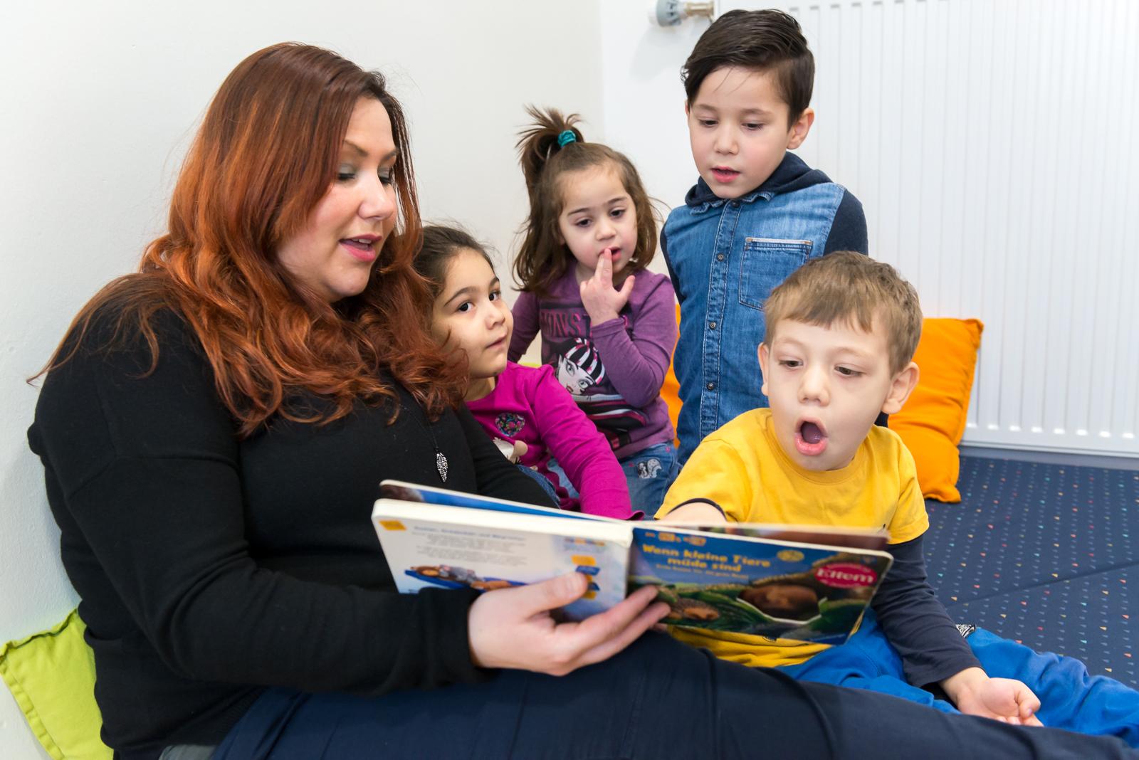 Eine junge Frau liest Kita-Kindern aus einem Buch vor.