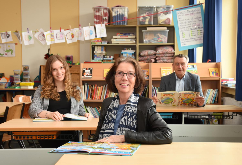 Theresa Rhau und Dorothea Kuttler von MENTOR Essen und Hans-Georg Adam von der Kinderstiftung Essen sitzen in einem Klassenzimmer der Großenbruchschule in Altenessen.