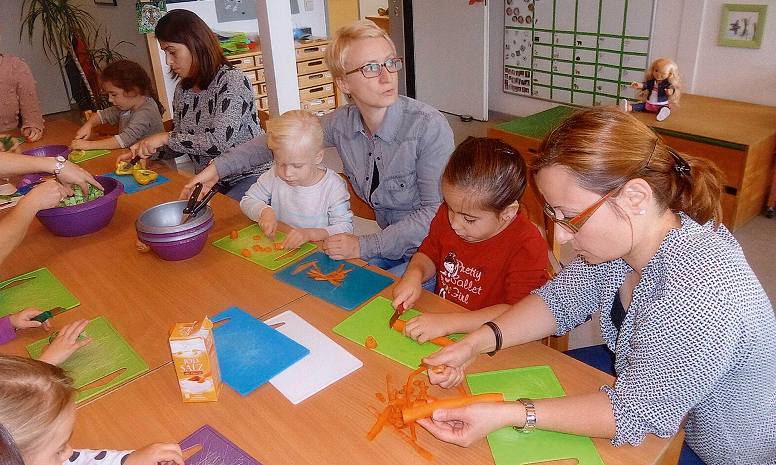 Eltern und Kinder schneiden Gemüse