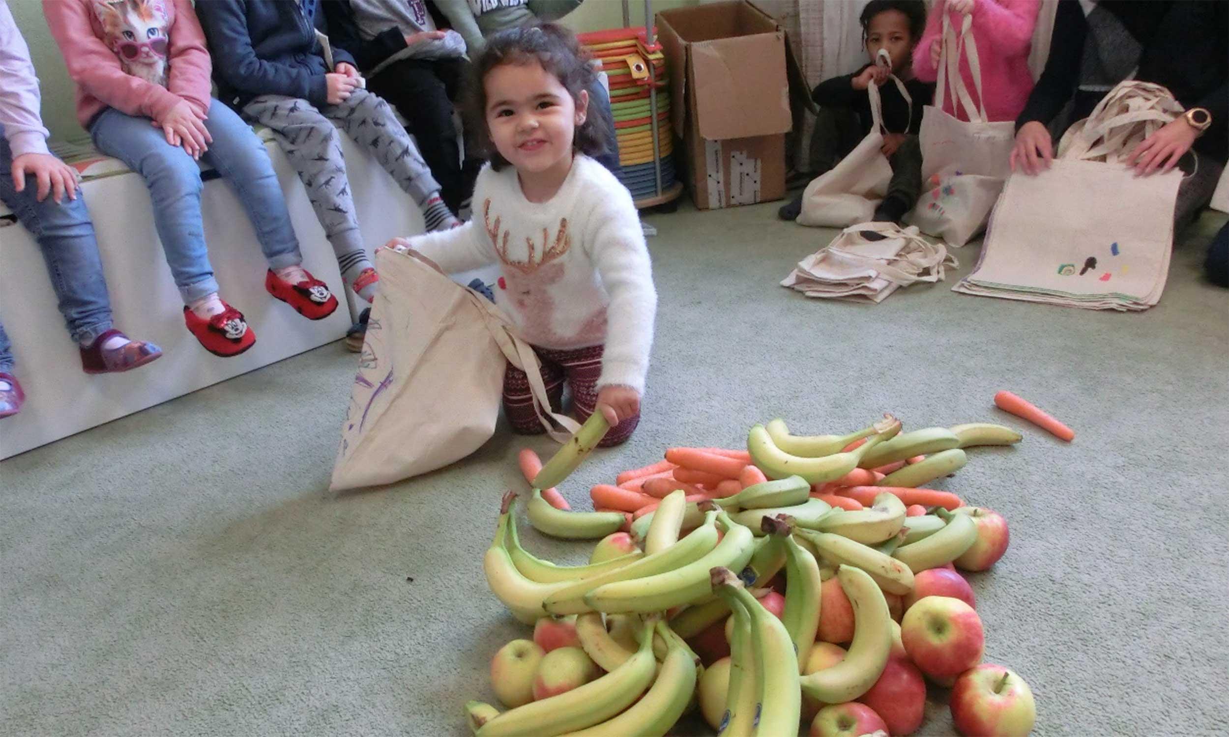 Kind füllt Stoffbeutel mit Obst