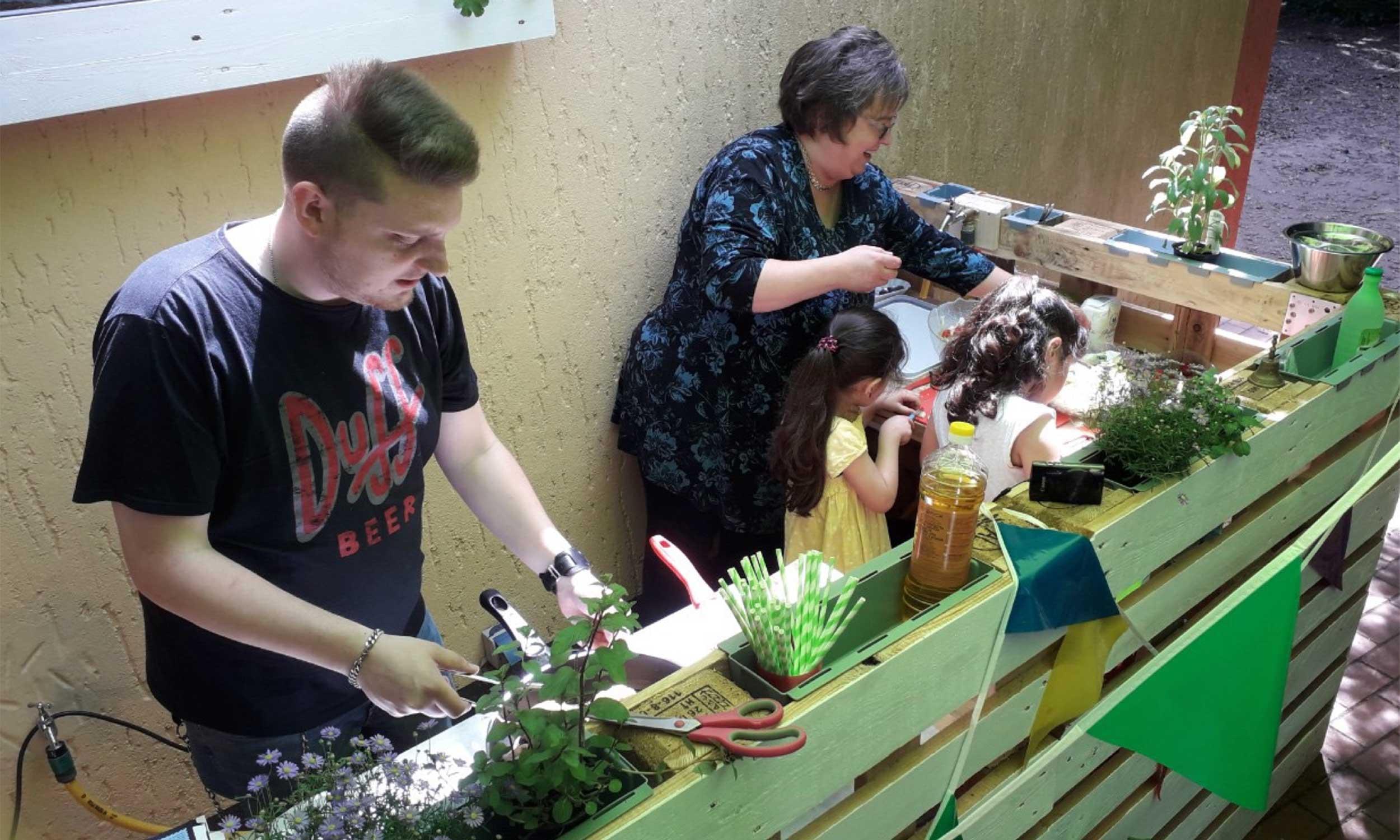 Kinder und Betreuer in einer Outdoor-Küche